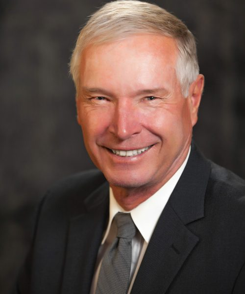 headshot of Larry Emerson smiling and wearing a suit