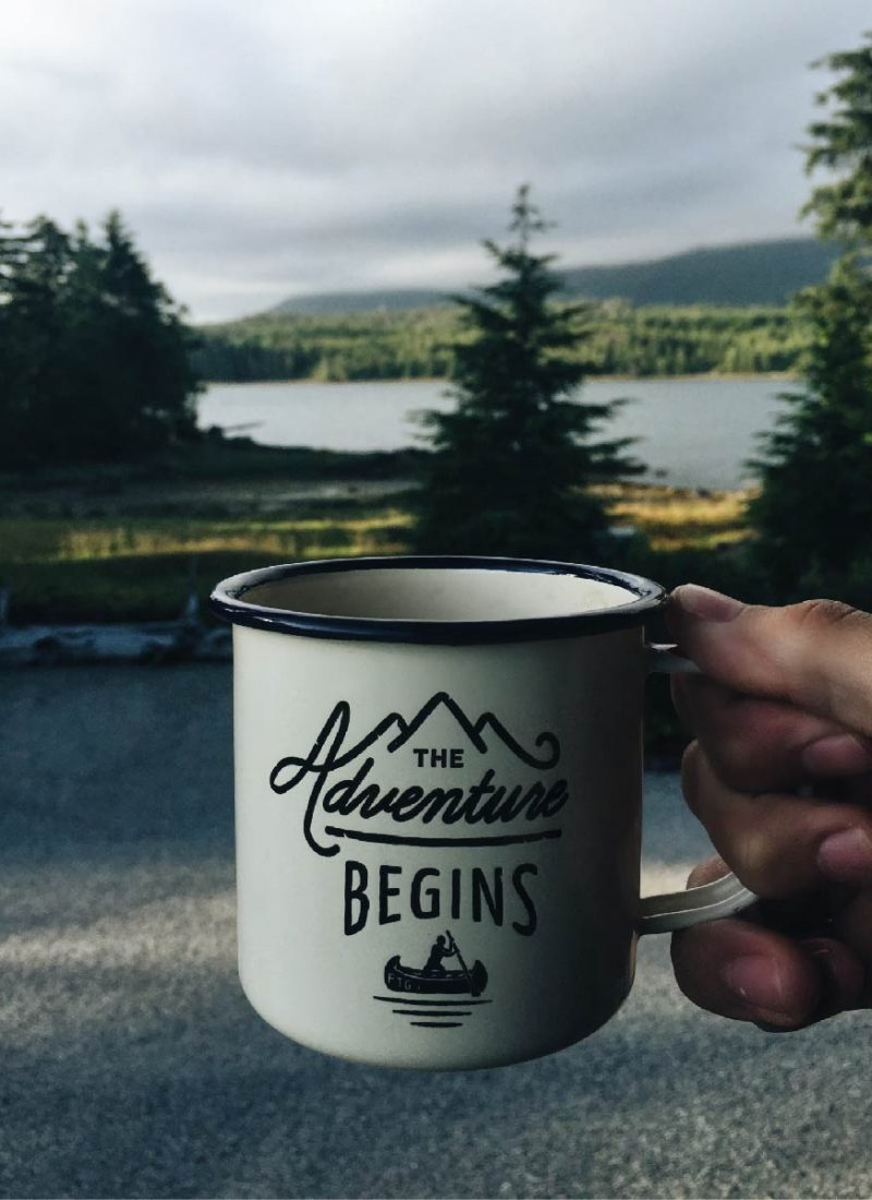 mountains in the background of a coffee cup that says the adventure begins